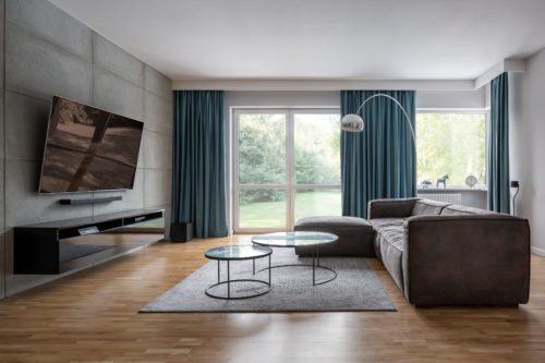 Modern living room with cement wall and corner sofa